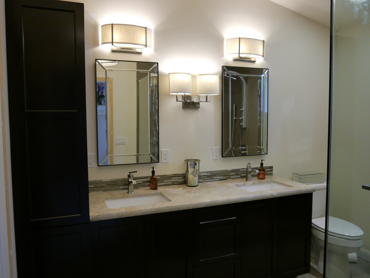 cherry cabinets in dark stain with marble countertop and leaded glass mirrors